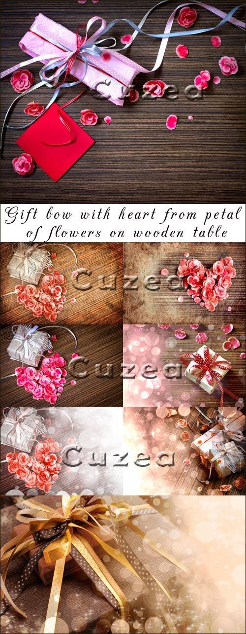 Подарок с сердцем из лепестков роз на деревянном столе