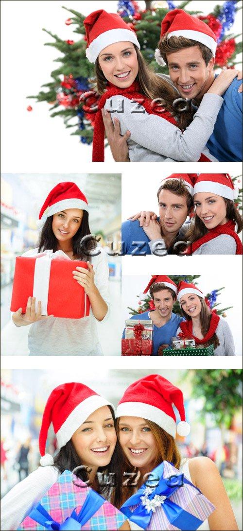 Девушки и парень в шапке санты с коробками подарков - Stock photo
